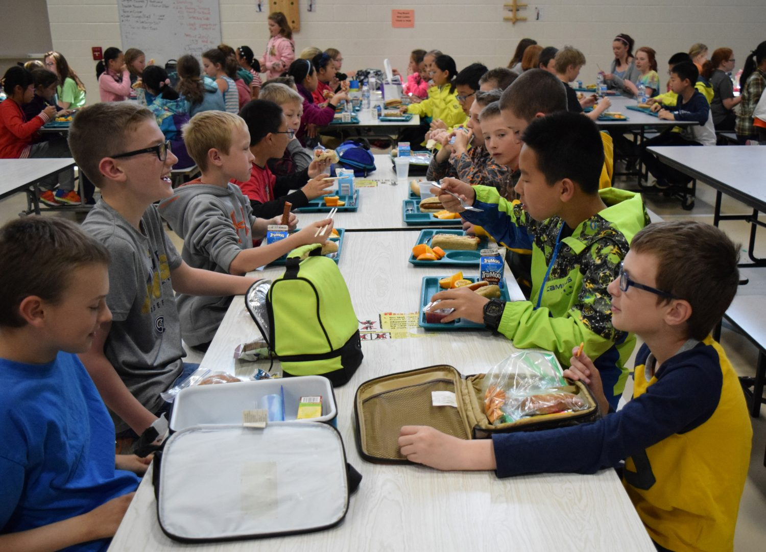 Chinese and American students chat during lunch at Madison Elementary in Marshfield on Monday, May 9.