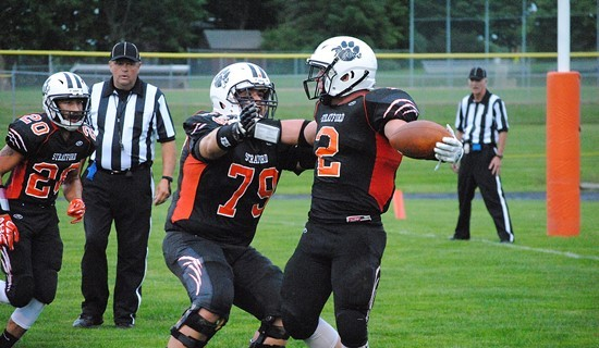 Stratford offensive lineman Tanner Weinfurtner (79) celebrates with Kam Bornbach (2) after Bornbach scored a touchdown during the first quarter of the Tigers' 24-13 win over Marathon on Friday night at Tiger Stadium in Stratford.