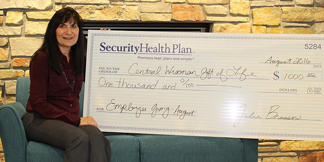 MCHS employee and kidney transplant recipient Cindy Dischinger holds a $1,000 check that Security Health Plan of Wisconsin Inc. is donating to Central Wisconsin Gift of Life as part of its Employee-Driven Corporate Giving program.