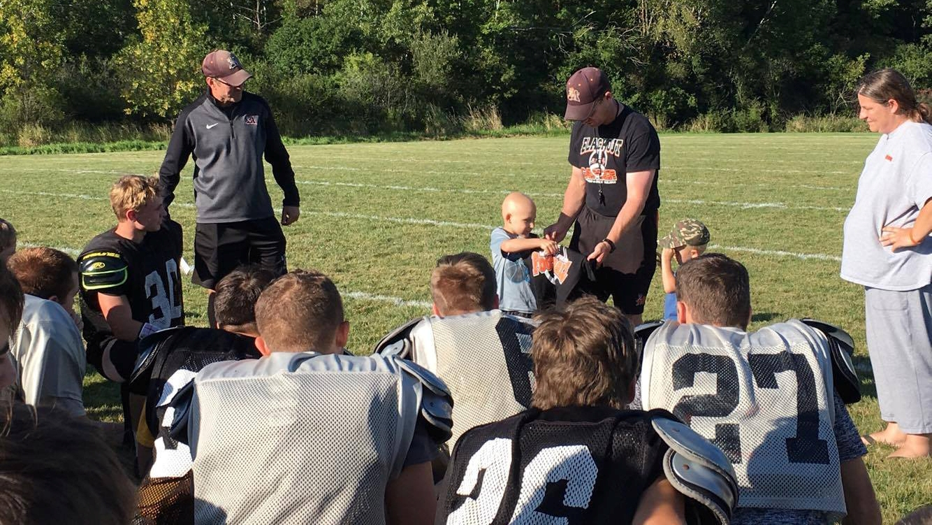 Beneficiary of this year's Blackout Cancer event, Carsyn Guyer (standing, second from left), attends practice with the Marshfield Tigers football team.