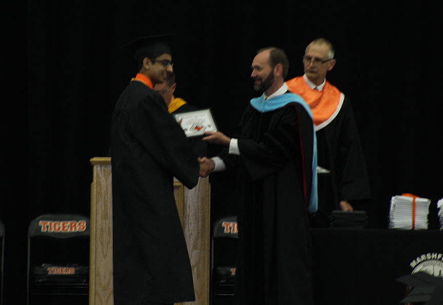 Muhammad Abidi receives his diploma from Superintendent Dr. Ryan Christianson.